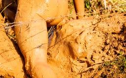 Atleta di funzionamento della traccia che attraversa una pozza sporca in un corridore del fango immagine stock