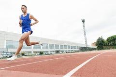 Atleta di pista attraente dell'uomo Running On Track Immagini Stock Libere da Diritti