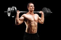 Atleta di sollevamento pesi che solleva un bilanciere Fotografie Stock