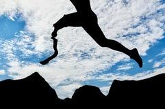 Atleta disabile con la gamba prostetica che salta attraverso il giorno della roccia Fotografia Stock Libera da Diritti