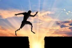 Atleta disabile con la gamba prostetica che salta sopra il precipizio sul tramonto Fotografia Stock