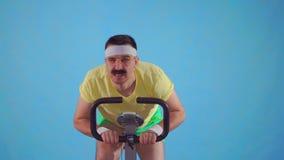 Atleta divertido del hombre joven de los años 80 con un bigote en la bicicleta estática en un fondo azul almacen de metraje de vídeo