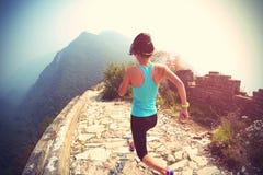 Atleta do corredor da mulher que corre na fuga no Grande Muralha chinês fotografia de stock