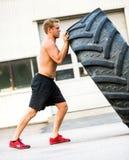 Atleta Doing Tire-Flip Exercise fuori della palestra Immagine Stock