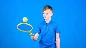 Atleta dzieciaka tenisowy kant na b??kitnym tle Tenisowy sport i rozrywka Ch?opiec dzieci bawi? si? tenis ?wiczy tenis obrazy royalty free