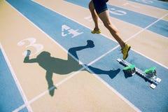 Atleta em sapatas do ouro que corre através da linha de partida Fotografia de Stock Royalty Free