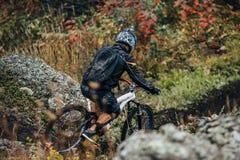Atleta en la bici a conseguir abajo de la montaña Fotografía de archivo
