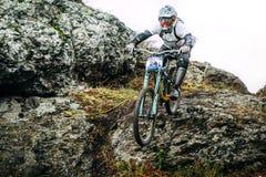 Atleta en la bici de montaña abajo del acantilado Fotografía de archivo libre de regalías