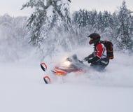Atleta en una moto de nieve que se mueve en el bosque del invierno Foto de archivo