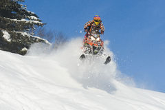 Atleta en una moto de nieve que se mueve en las montañas Imagen de archivo libre de regalías