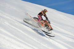 Atleta en una moto de nieve que se mueve en las montañas Fotografía de archivo