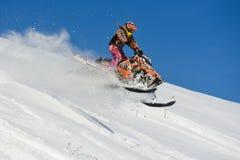 Atleta en una moto de nieve que se mueve en las montañas Fotos de archivo