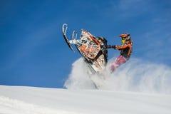 Atleta en una moto de nieve que se mueve en las montañas Fotos de archivo libres de regalías