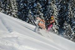 Atleta en una moto de nieve que se mueve en las montañas Imagenes de archivo