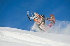 Atleta en una moto de nieve que se mueve en las montañas Foto de archivo