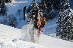 Atleta en una moto de nieve que se mueve en las montañas Imagen de archivo
