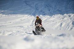 Atleta en una moto de nieve que se mueve en las montañas Imágenes de archivo libres de regalías