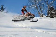 Atleta en una moto de nieve que se mueve en las montañas Fotografía de archivo libre de regalías