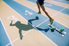 Atleta en zapatos del oro que esprinta a través de línea de salida Fotografía de archivo libre de regalías