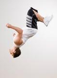 Atleta experto que hace voltereta en mid-air imagen de archivo libre de regalías