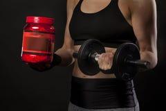 Atleta fêmea com suplementos e proteínas ao halterofilismo fotografia de stock