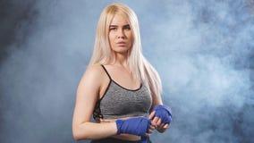 Atleta fêmea concentrado caucasiano novo que envolve seus punhos pelas ataduras elásticas azuis Movimento lento vídeos de arquivo