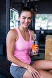 Atleta fêmea de sorriso que guarda a garrafa de água Imagem de Stock Royalty Free