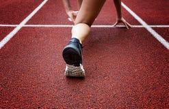 Atleta fêmea não identificado que lança-se fora da linha do começo em uma raça Imagem de Stock Royalty Free
