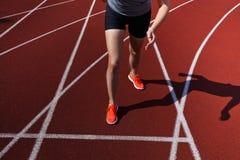 Atleta fêmea não identificado que lança-se fora da linha do começo em uma raça Foto de Stock