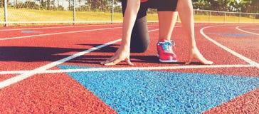 Atleta fêmea na linha de partida de uma trilha do estádio imagem de stock