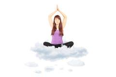 Atleta fêmea novo no sportswear que senta-se em nuvens e em meditat Imagem de Stock Royalty Free