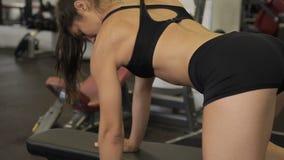 Atleta fêmea novo que faz o exercício da fileira do peso no gym dentro vídeos de arquivo