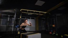Atleta fêmea novo que faz um salto da caixa no gym - focalize na mulher vídeos de arquivo