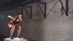 Atleta fêmea novo que faz um salto da caixa no gym Movimento lento video estoque