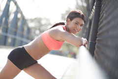 Atleta fêmea novo que inclina-se em trilhos Foto de Stock Royalty Free