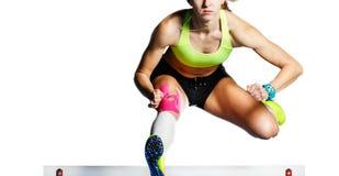 Atleta fêmea novo que salta sobre o obstáculo na sprint imagem de stock