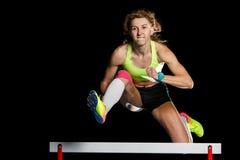 Atleta fêmea novo que salta sobre o obstáculo na sprint foto de stock royalty free