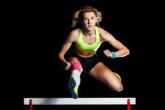Atleta fêmea novo que salta sobre o obstáculo na sprint fotografia de stock