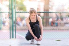 Atleta fêmea que amarra laços para movimentar-se imagens de stock royalty free