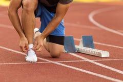 Atleta fêmea que amarra laços para movimentar-se Mulher que movimenta-se em uma pista de atletismo Sapatas Running Saúde da aptid Fotografia de Stock Royalty Free