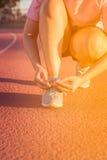 Atleta fêmea que amarra laços para movimentar-se, por do sol Fotos de Stock Royalty Free