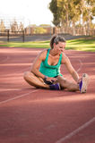 Atleta fêmea que estica em uma pista de atletismo foto de stock