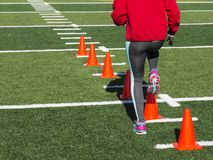 Atleta fêmea que executa brocas de corrida sobre cones fotos de stock
