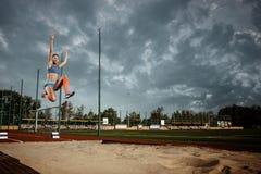 Atleta fêmea que executa um salto longo durante uma competição foto de stock