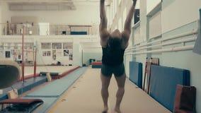 Atleta fêmea que exercita no gym, correndo acima e fazendo um salto mortal dobro para trás vídeos de arquivo