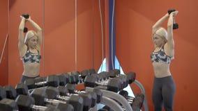 Atleta fêmea que faz o exercício aéreo da extensão do tríceps no gym video estoque