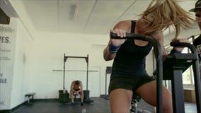 Atleta fêmea que faz o exercício intenso na bicicleta do gym com treinador