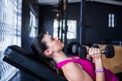 Atleta fêmea que guarda o peso ao encontrar-se na imprensa de banco imagem de stock