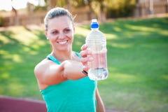 Atleta fêmea que guarda uma garrafa de água foto de stock
