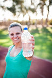 Atleta fêmea que guarda uma garrafa de água fotografia de stock royalty free